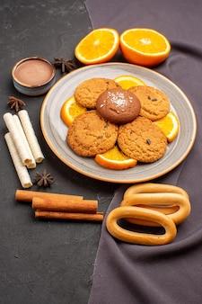 正面図暗い背景に新鮮なスライスしたオレンジとおいしいクッキーシュガークッキーフルーツビスケット甘い