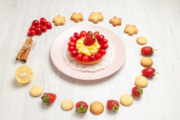 正面図白い机の上の果物とケーキとおいしいクッキーフルーツティービスケットデザート