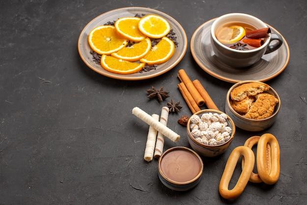 Вид спереди вкусное печенье с нарезанными апельсинами и чашкой чая на темном фоне сахарное печенье фруктовое сладкое печенье