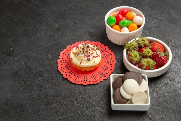 Front view delicious cream cake with candies cookies and fruits on grey background cake cream biscuit sweet cookie dessert