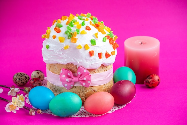 Front view delicious cream cake with colored eggs and candle on pink background sugar cake pie sweet colourful ornate novruz spring holiday
