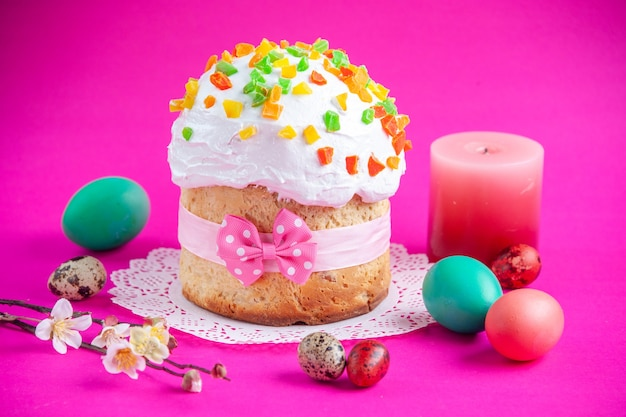 Front view delicious cream cake with colored eggs and candle on pink background sugar cake pie sweet dessert colourful ornate novruz spring holiday Premium Photo