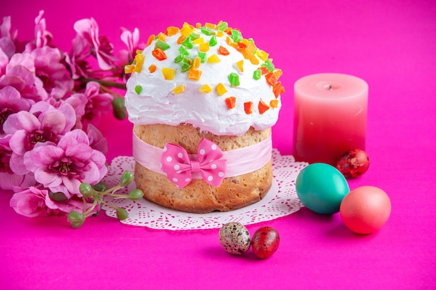 Front view delicious cream cake with colored eggs and candle on pink background sugar cake pie sweet dessert colourful ornate novruz spring holidays