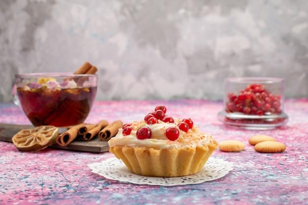Вид спереди восхитительный кремовый торт со свежей красной клюквой, корицей и чаем на светлом столе, сладкий сахар