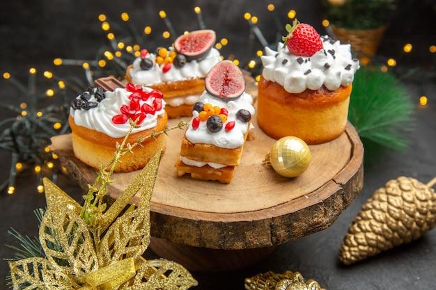 Vista frontale deliziose torte alla crema intorno ai giocattoli dell'albero di capodanno su una torta da scrivania scura dolce crema fotografica dessert
