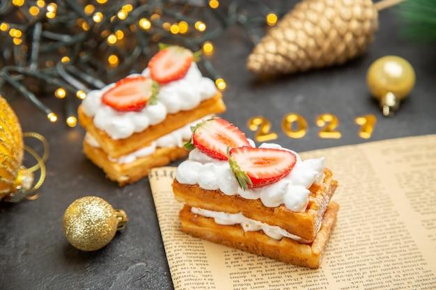 暗い背景のケーキの甘い写真クリームデザートの新年の木のおもちゃの周りのイチゴと正面図おいしいクリームケーキ