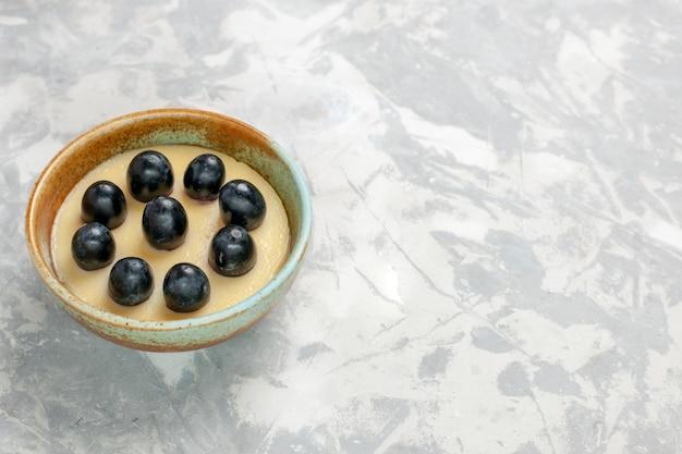 Vista frontale delizioso dessert alla crema con l'uva in cima all'interno della piccola pentola sulla superficie bianca