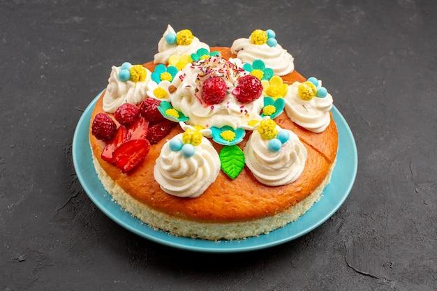 Вид спереди вкусный кремовый пирог с фруктами на темном пространстве