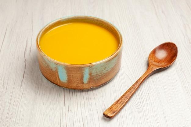Vista frontale deliziosa zuppa di crema zuppa di colore giallo su una scrivania bianca zuppa di salsa pasto crema piatto per la cena