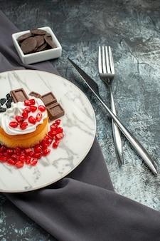 Vista frontale deliziosa torta cremosa con cioccolato e uvetta su uno sfondo chiaro-scuro biscotto dolce biscotto dolce zucchero