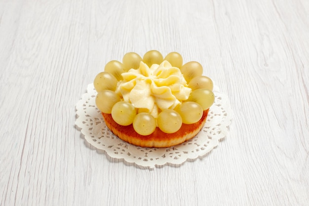正面図白い机の上に緑のブドウとおいしいクリーミーなケーキフルーツクリームケーキビスケットクッキー