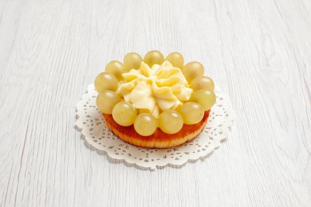 Vista frontale deliziosa torta cremosa con uva verde su scrivania bianca torta alla crema di frutta biscotto biscotto