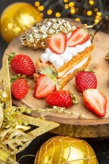 暗い背景の休日の木のおもちゃの周りのおいしいクリーミーなケーキの正面図デザートケーキ甘いフォトクリーム