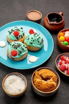 正面図暗い背景にキャンディーとおいしいクリーミーなケーキキャンディービスケットケーキデザートクッキーの色