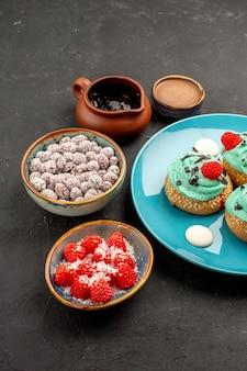 正面図暗い机の上のキャンディーとおいしいクリーミーなケーキデザートケーキビスケットキャンディークッキーの色