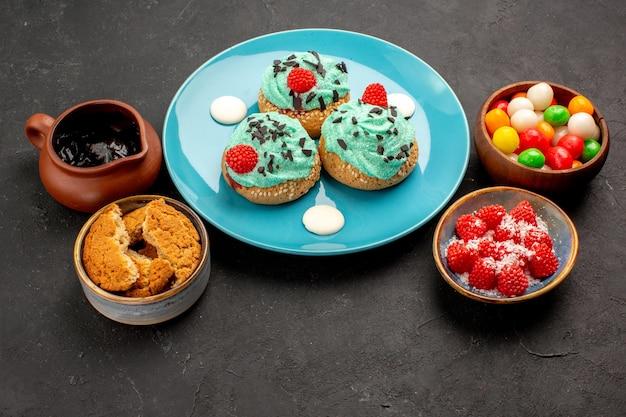 어두운 회색 배경 캔디 비스킷 케이크 디저트 쿠키 색상에 사탕이 있는 맛있는 크림 케이크 전면 보기