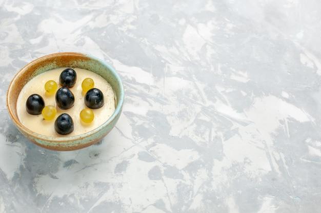 正面図白い表面の小さな鍋の中に果物が上にあるおいしいクリーミーなデザート