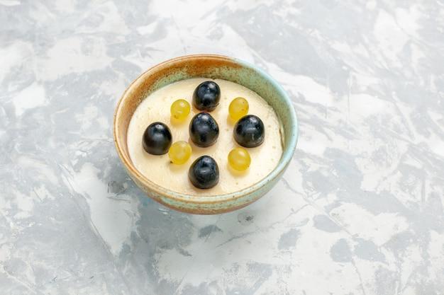 Vista frontale delizioso dessert cremoso con frutta in cima all'interno di una piccola pentola sulla superficie bianca