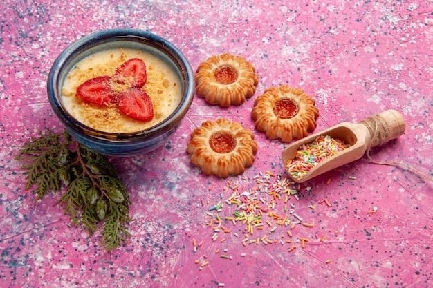 밝은 분홍색 벽에 빨간색 슬라이스 딸기와 쿠키가있는 전면보기 맛있는 크림 디저트 디저트 아이스크림 크림 달콤한 베리 과일