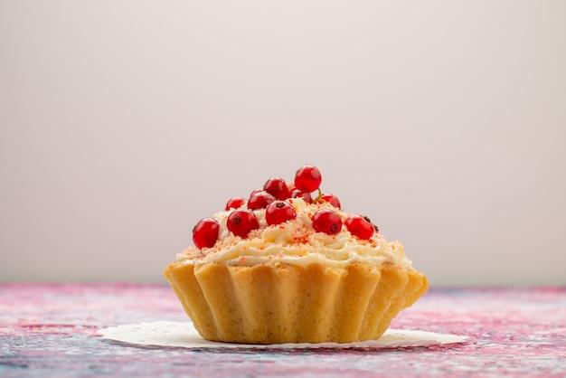 ライトデスクフルーツに分離されたクリームの新鮮な赤いクランベリーと正面のおいしいdケーキ