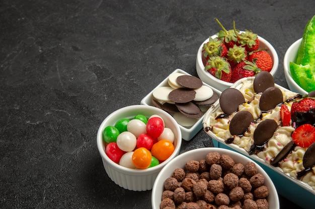 Вид спереди вкусный десерт с конфетами, печеньем и клубникой на темном фоне, ореховое печенье, сладкое фруктовое печенье, сахар