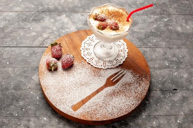 灰色の机の上にイチゴと正面のおいしいデザート