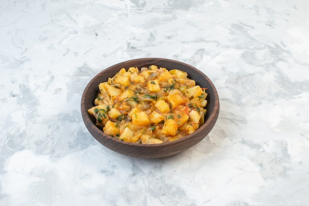 Front view of delicious dinner with potatoes vegetables green in a brown bowl on ice background with free space