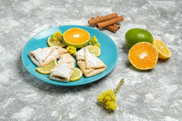 Vista frontale deliziosi pasticcini della pasta con le fette di limone sulla parete bianca chiara pasticceria zucchero cuocere la torta pasta torta dolce biscotto