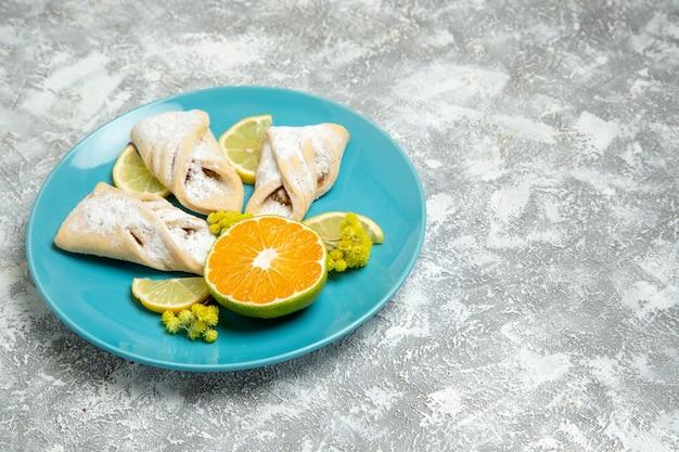 Vista frontale deliziosi pasticcini della pasta con fette di limone sulla parete bianca pasticceria zucchero cuocere la torta pasta dolce torta