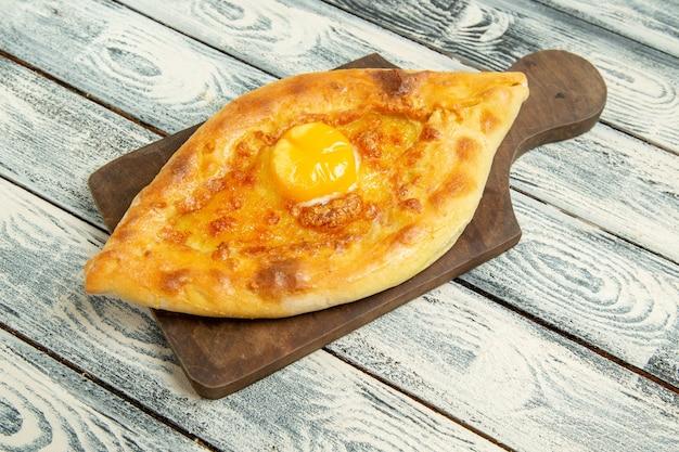 Vista frontale delizioso pane all'uovo cotto sulla scrivania rustica grigia
