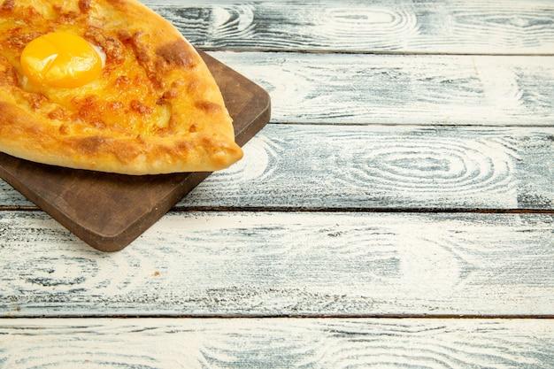 素朴な机の上で焼き上げた美味しい卵パンの正面図