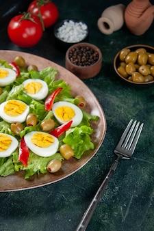 전면보기 맛있는 계란 샐러드는 어두운 배경에 그린 샐러드와 올리브로 구성