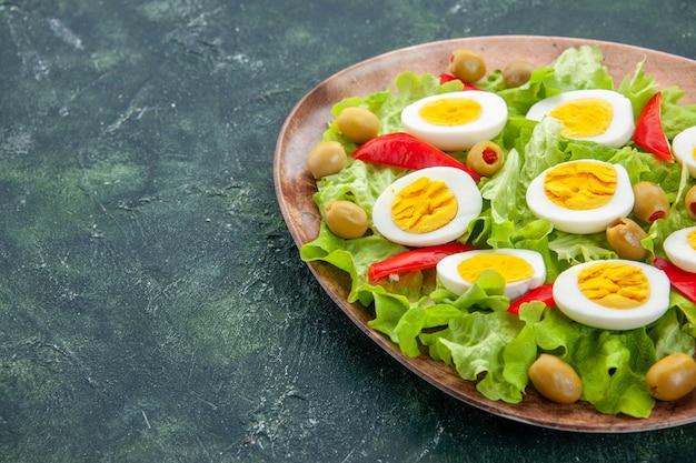 Вид спереди вкусный яичный салат с зеленым салатом и оливками на темно-синем фоне
