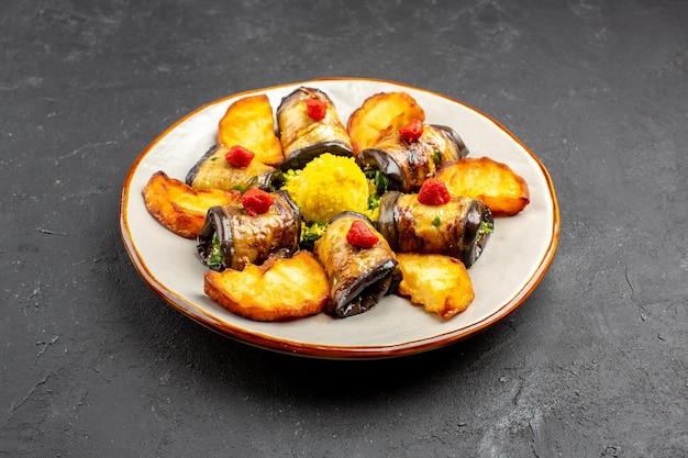 Vista frontale deliziosi involtini di melanzane piatto cotto con patate al forno sullo sfondo scuro piatto da pasto che cucina il cibo cuocere le patate fritte