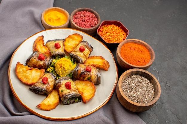 Vista frontale deliziosi involtini di melanzane cucinati con patate al forno e condimenti su spazio buio dark