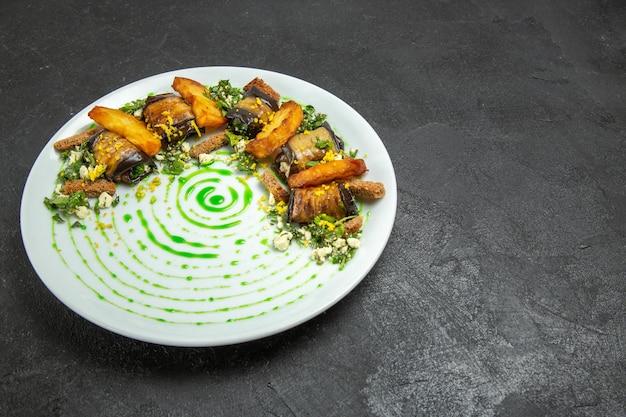 正面図暗い床の皿の皿の内側のプレートの中にベイクドポテトが入ったおいしいナスロール料理ディナーポテト野菜