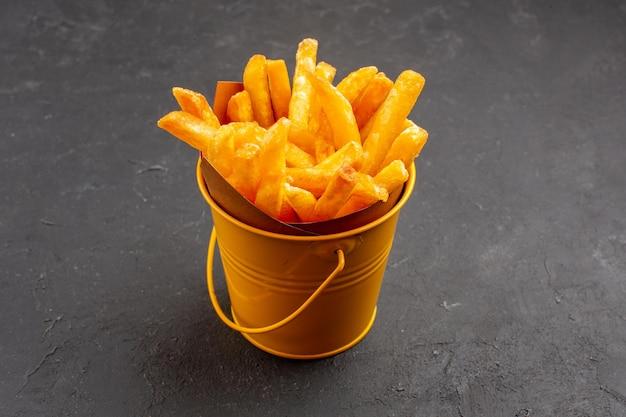 Vista frontale deliziose patatine fritte all'interno di un piccolo cestino su uno spazio buio dark