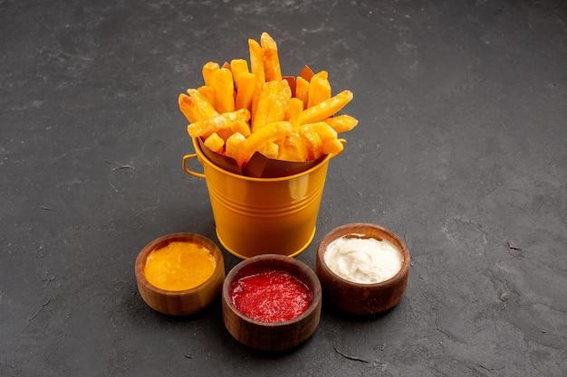 어두운 공간에서 케첩 겨자와 마요네즈를 곁들인 전면보기 맛있는 감자 튀김