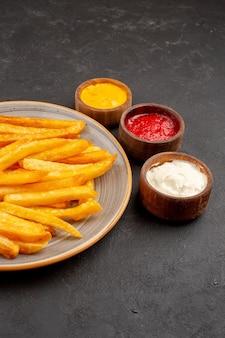 Vista frontale deliziose patatine fritte con condimenti su spazio buio