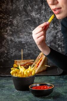여성 어두운 표면에 의해 먹는 조미료와 전면보기 맛있는 감자 튀김