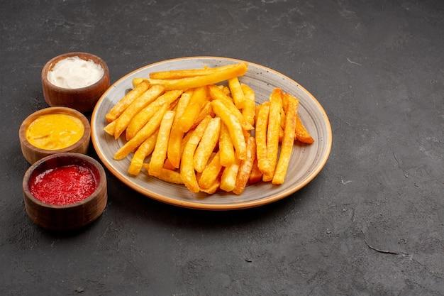 Вид спереди вкусный картофель фри с приправами на темном пространстве