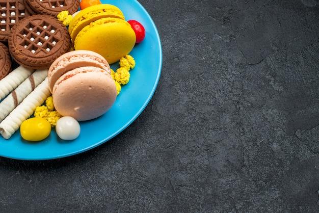 Vista frontale deliziosi macarons francesi con caramelle e biscotti al cioccolato su scrivania grigia biscotto zucchero torta dolce cuocere i biscotti