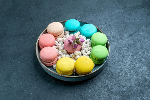 Front view delicious french macarons with candies inside tray on dark space