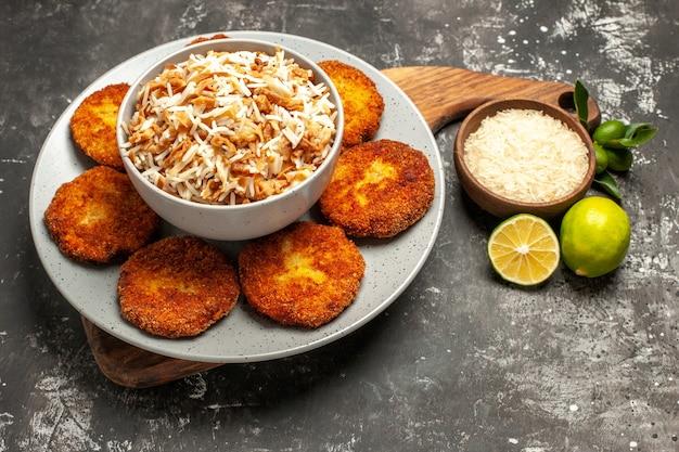 Vista frontale deliziose cotolette fritte con riso cotto su carne di polpetta piatto superficie scura