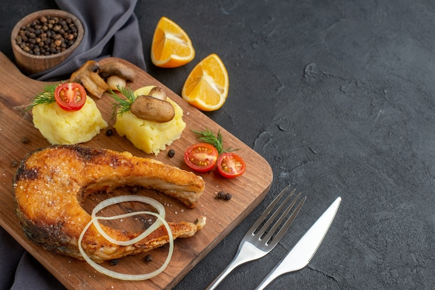 Front view of delicious fried fish meal with mushrooms vegetables cheese on wooden board lemon slices pepper on dark color towel cutlery set on the right side on black distressed surface