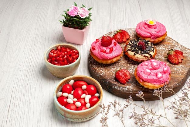 Vista frontale deliziose torte alla frutta dolci cremosi con caramelle e frutta su sfondo bianco biscotto alla crema dessert torta dolce tè