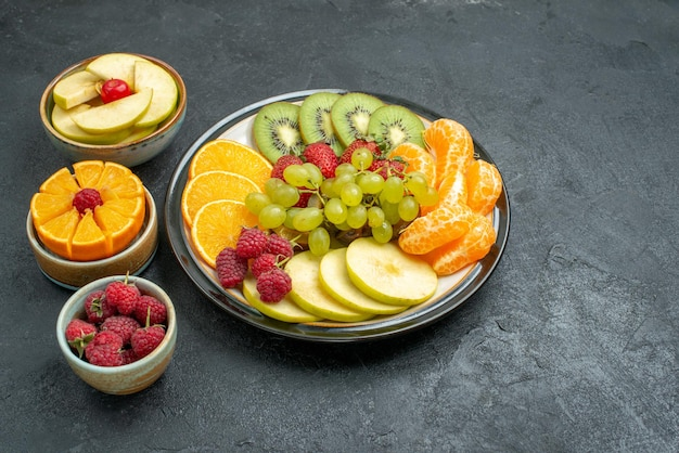 Front view delicious fruit composition fresh and sliced fruits on a dark background health ripe fresh fruit mellow