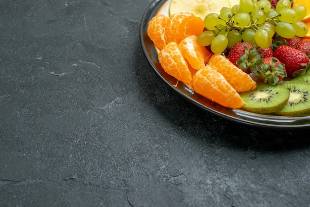 Front view delicious fruit composition fresh sliced and mellow fruits on dark background ripe fresh health diet fruit