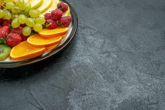 Vista frontale deliziosa composizione di frutta fresca affettata e frutta dolce su sfondo scuro frutta fresca e matura per la dieta salutare