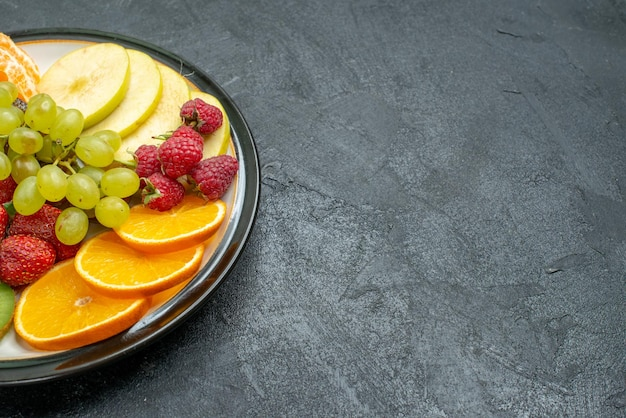 Vista frontale deliziosa composizione di frutta fresca affettata e frutta dolce sullo sfondo scuro dieta salutare fresca e matura
